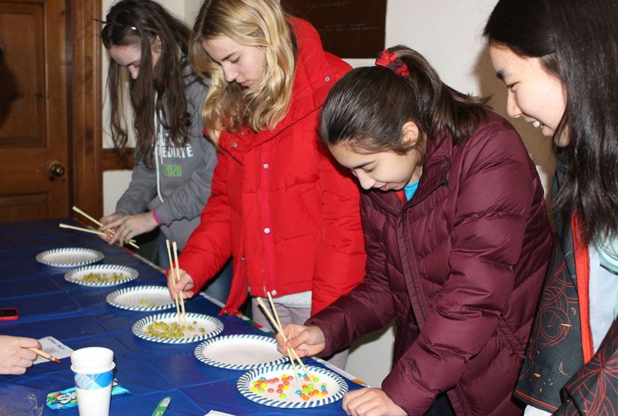The International Bazaar featured fun stations throughout Schoolhouse — here, Rebecca C. '23, Cameron H. '23, and Leah N. '22 race against the clock to see how many pieces of food they can pick up using chopsticks while Sabrina C. '22 cheers them on.
