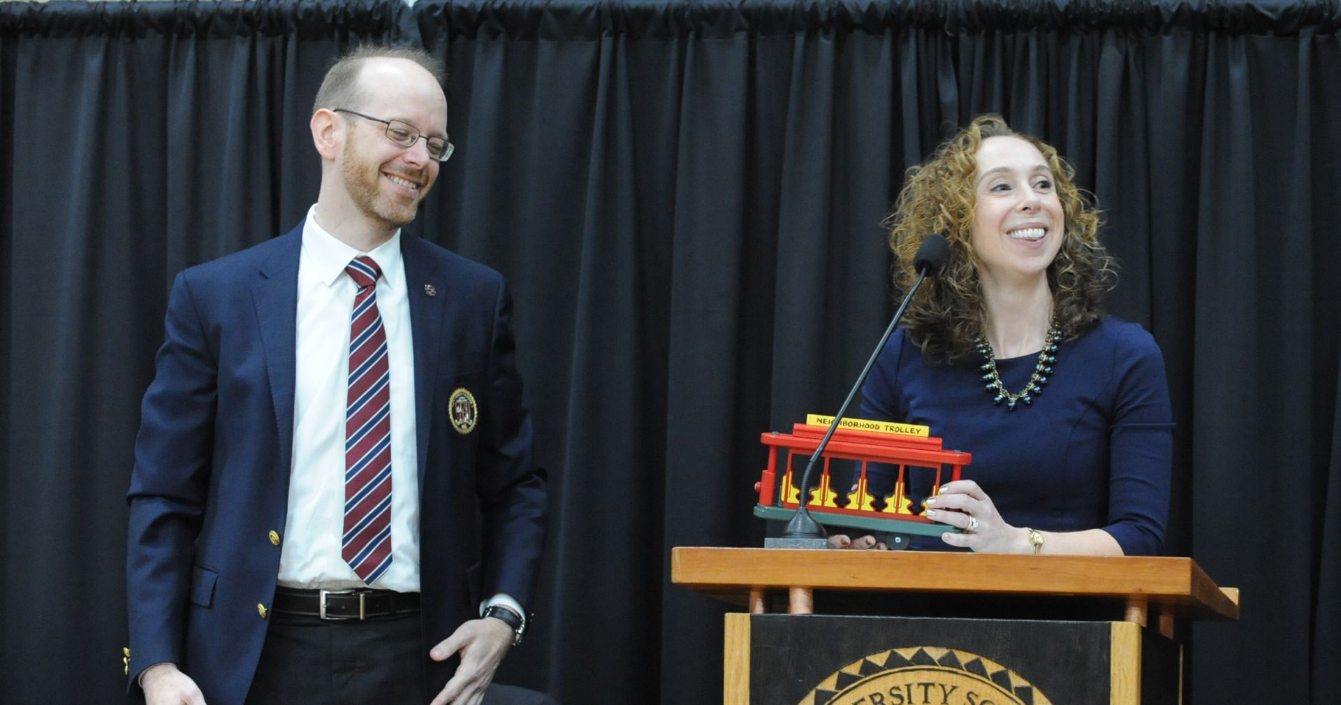 Faculty representative Lisa Ulery presents a replica of the Mr. Rogers' neighborhood trolley to the new Head of School.