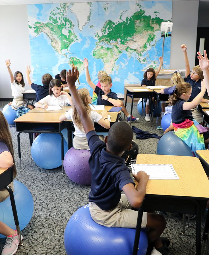 Elementary school students raising their hands to answer a teacher's question in a science class at Second Baptist School