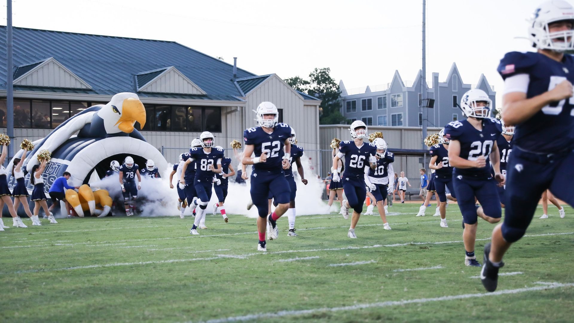 Football players running out of the eagle and onto the field for a game at SBS