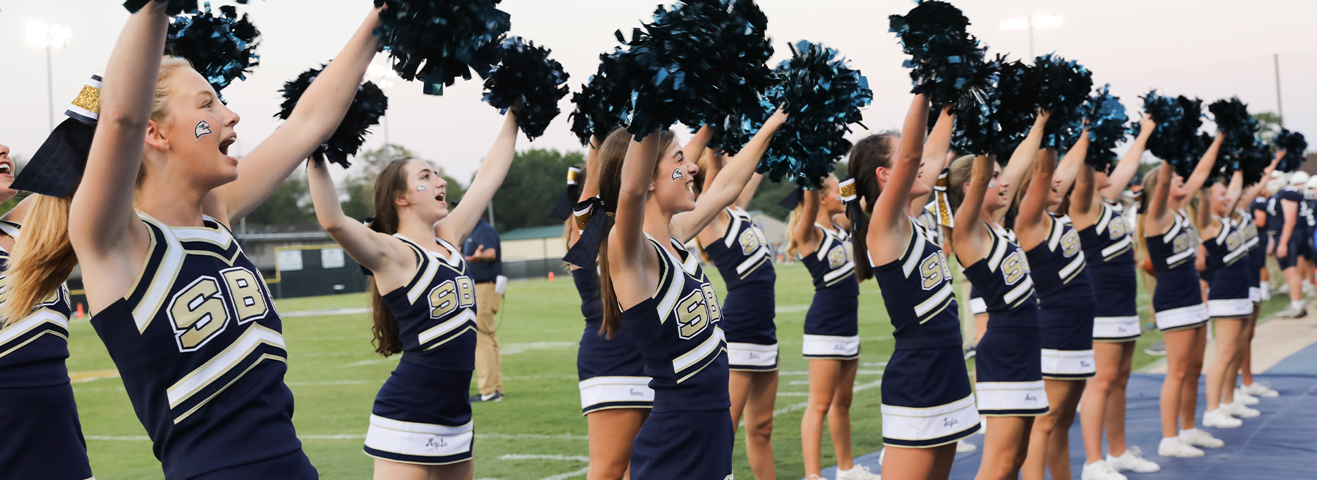 High school cheerleaders supporting the SBS football team at a game