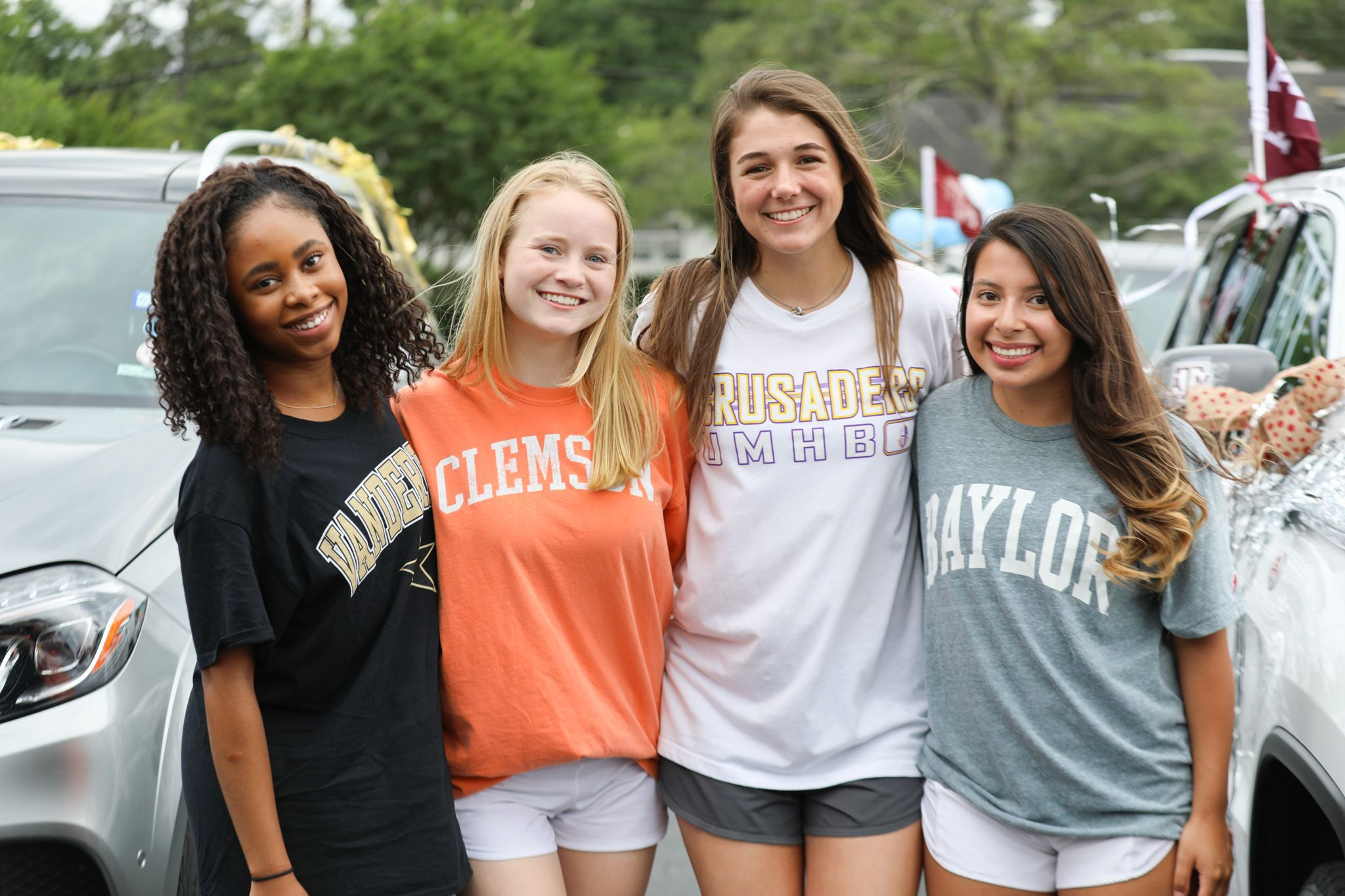 High school senior girls wearing their college t-shirts gathered together in the parking lot at Second Baptist School