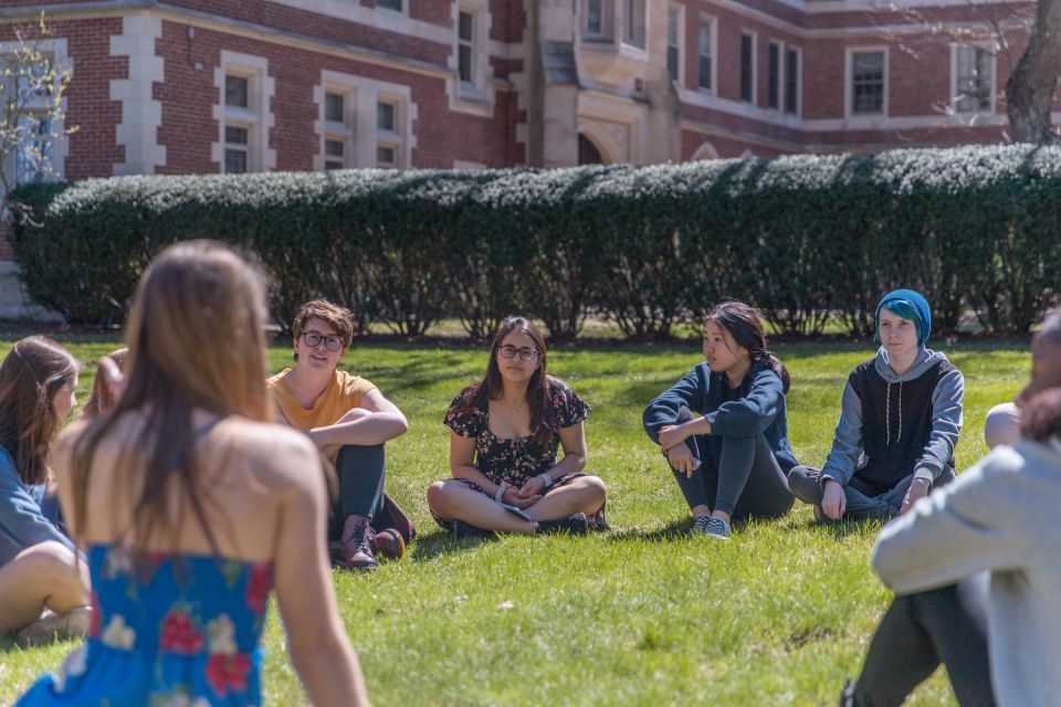 Group of students sits in a circle in the grass