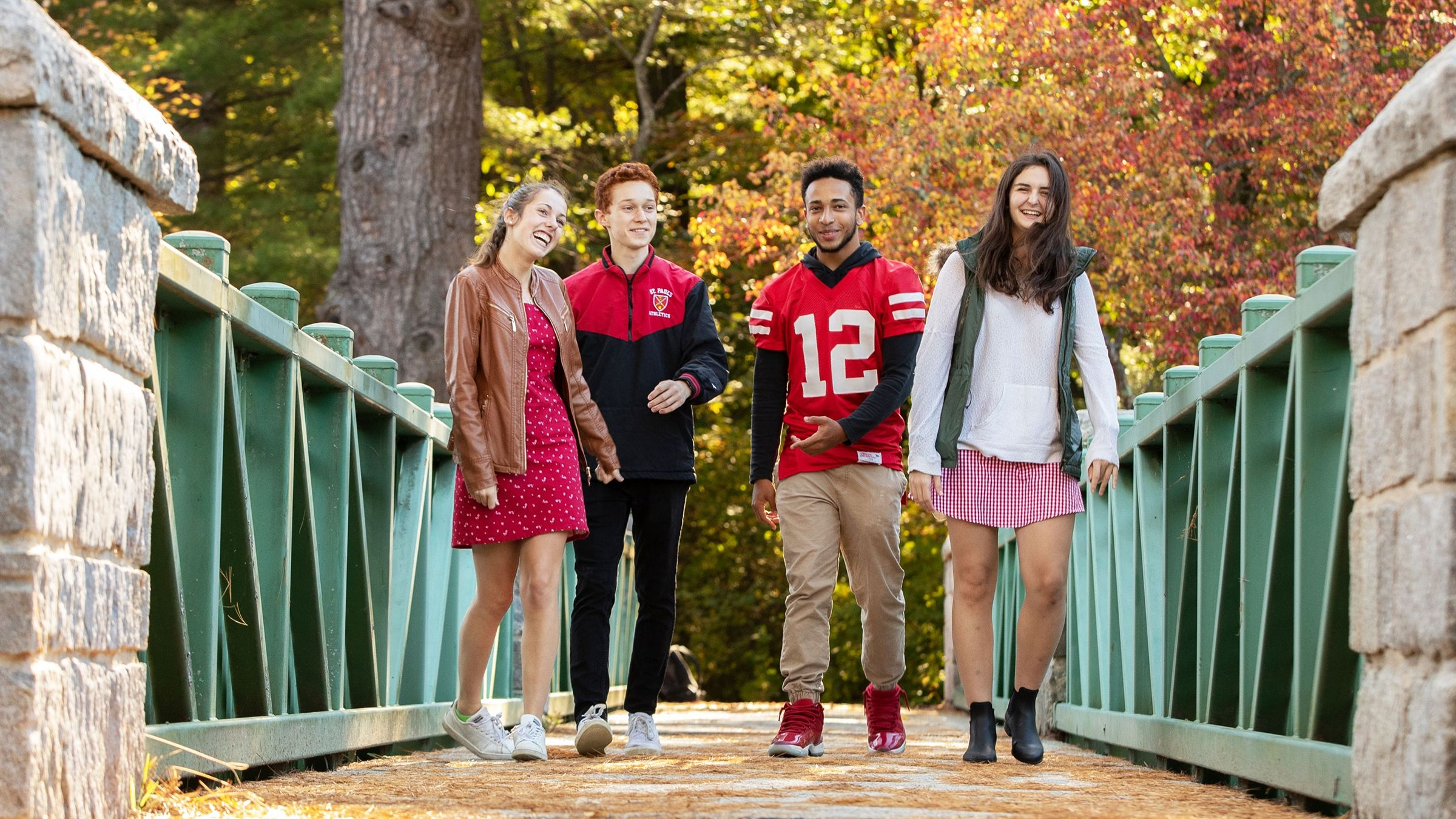 4 students walking across a bridge