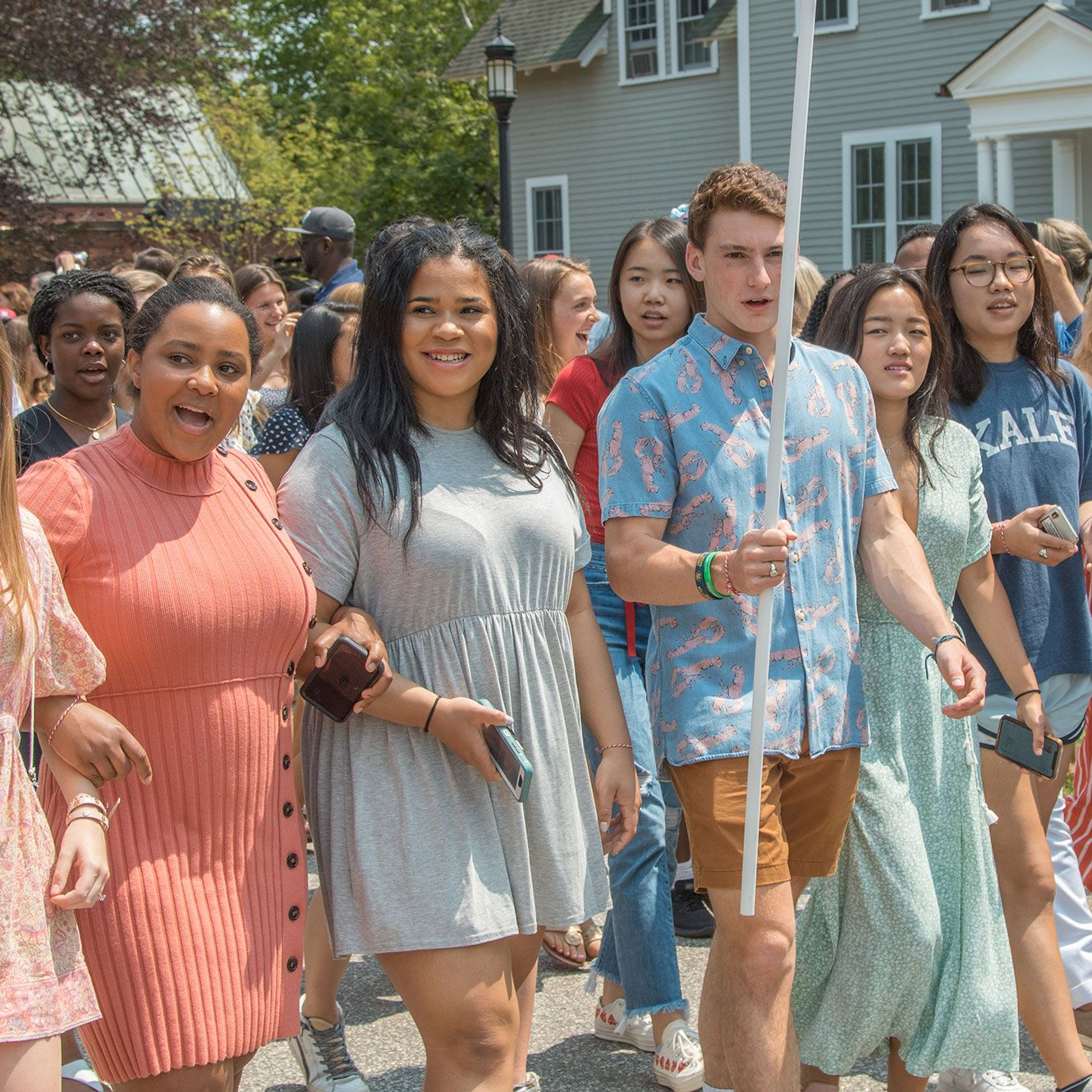 Recent alumni walking in parade on campus