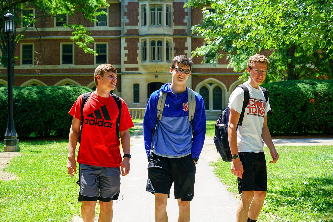 3 boys outside, walking along campus