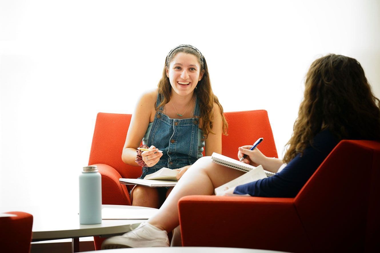 Girl sitting in lounge chair doing homework, and laughing with a friend