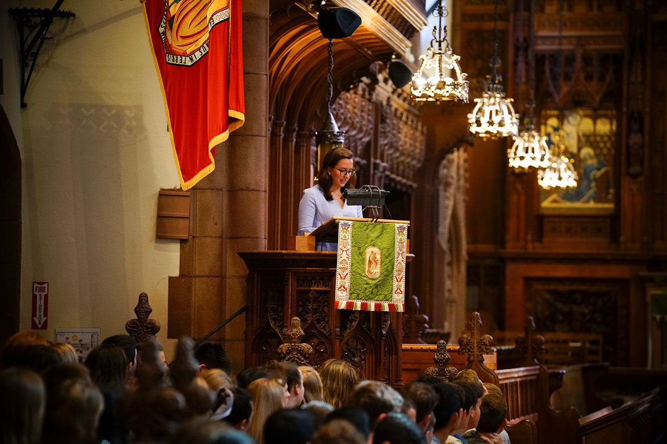 Woman standing and speaking at podium in chapel