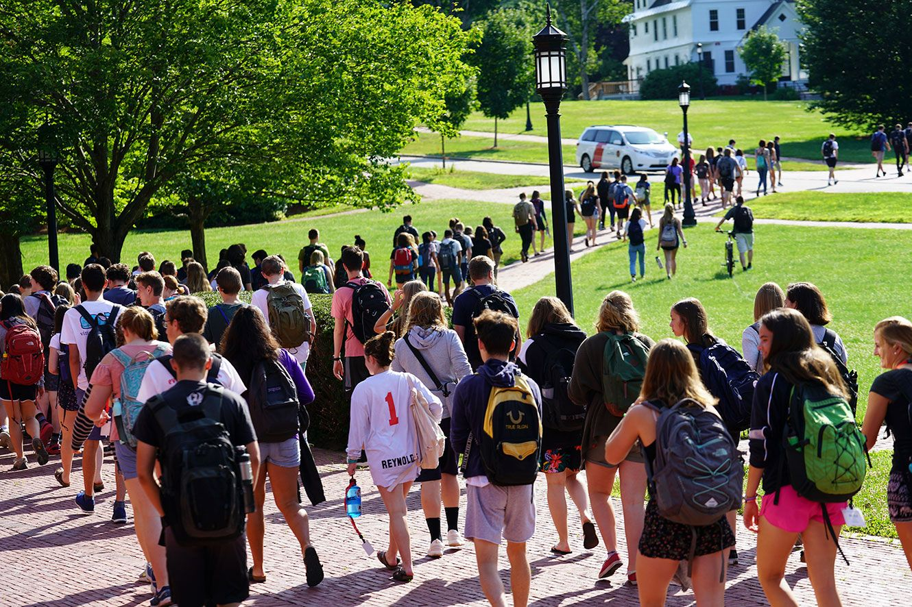 Large group of students snaking along pathway through campus