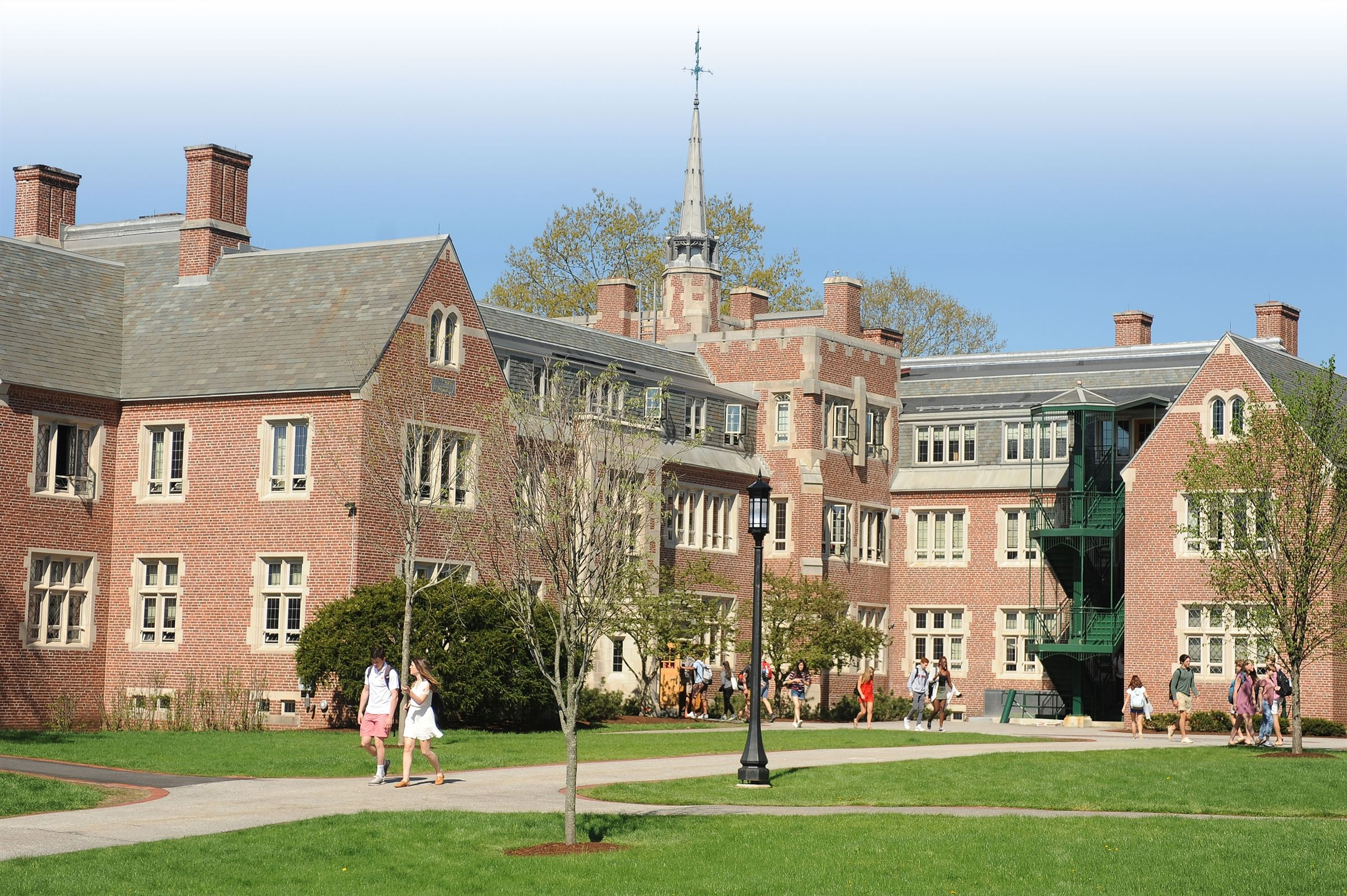 Students walking across campus in front of a large brick building