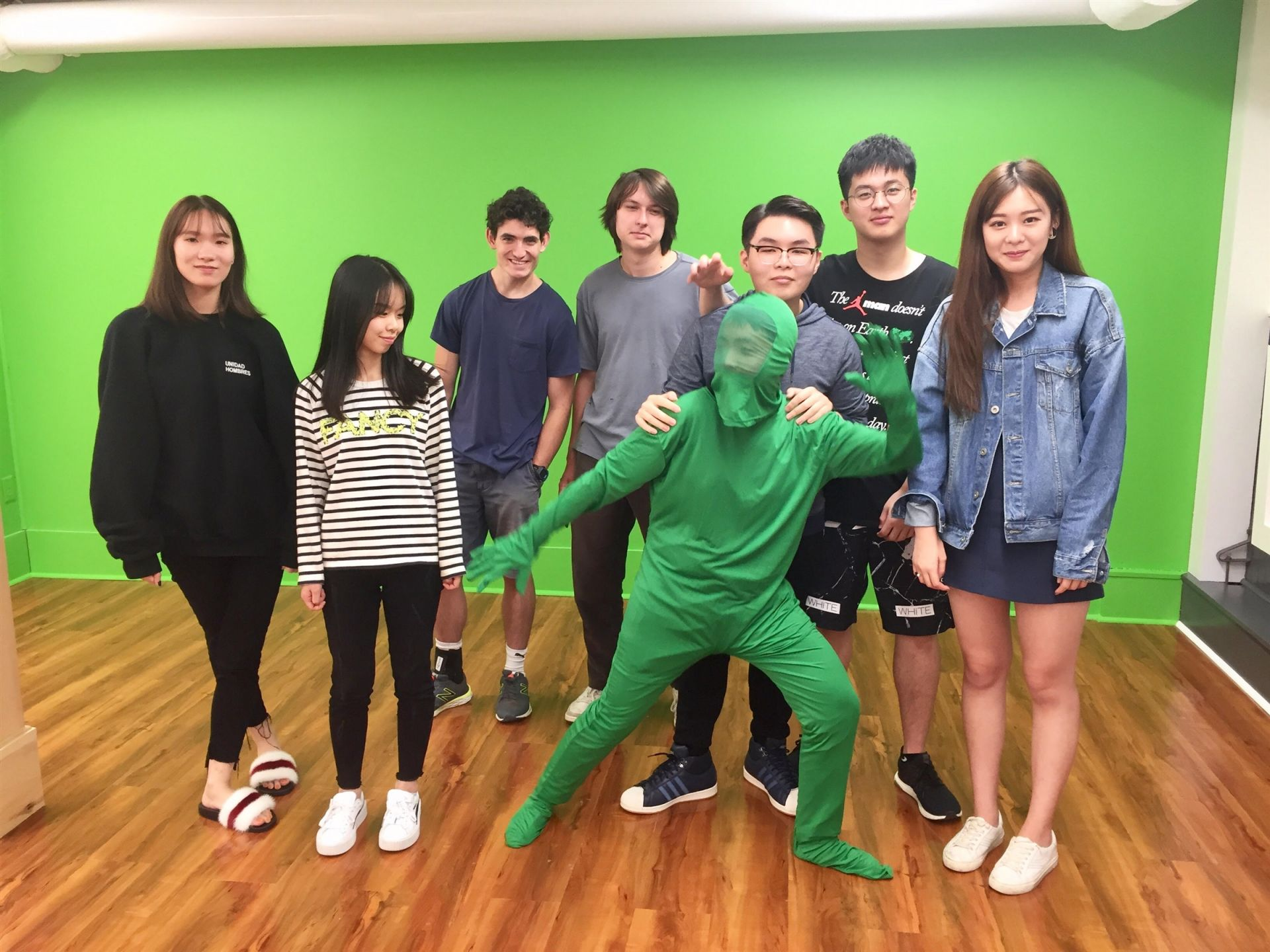 Filmmaking students standing in front of the wall-to-ceiling green screen.