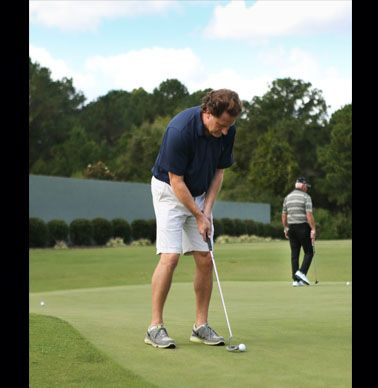 Faculty Team member Ben Rous practices his putting.