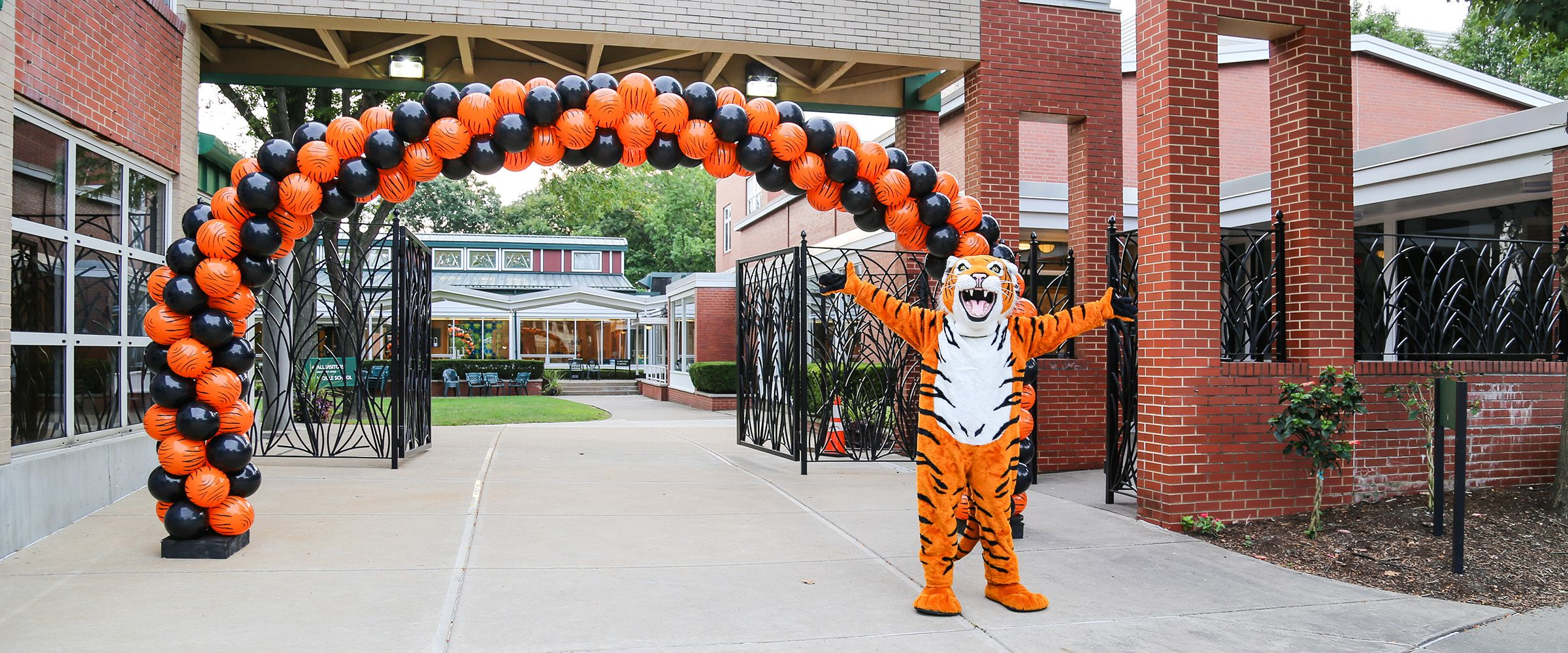 The Ellis tiger poses in front of The Ellis School.