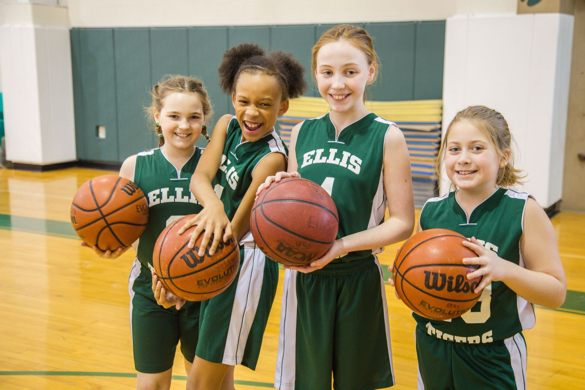 This is a picture of middle school girls posing with basketballs.