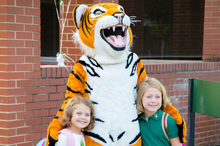 This is a photo of elementary students smiling with the Ellis tiger.