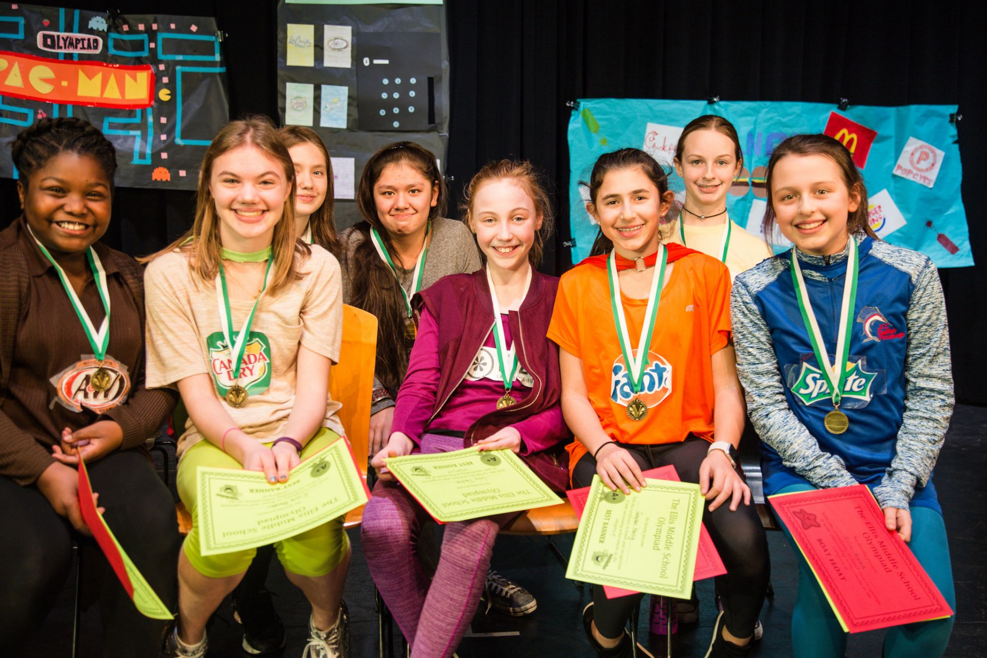 This is a photo of middle school students smiling after winning a competition.