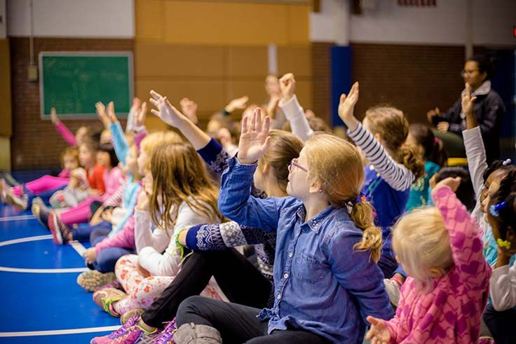 This is a picture of elementary students raising their hands.