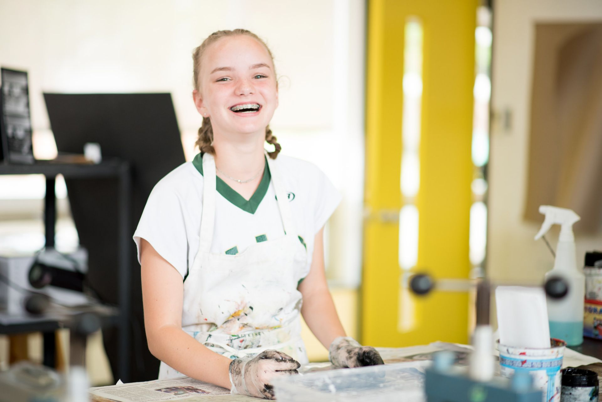 This is a photo of a high school student smiling in the art lab.