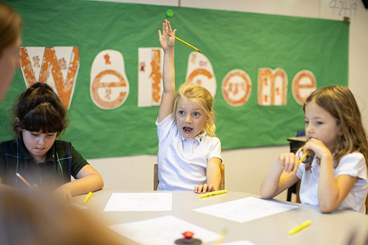 This is a photo of a Lower School girl excitedly raising her hand in class.