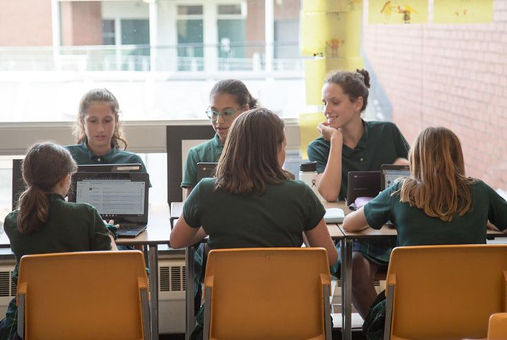 This is a photo of Middle School girls working together in a computer lab.