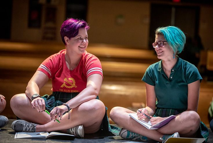 Two Upper School students sitting cross-legged on a stage