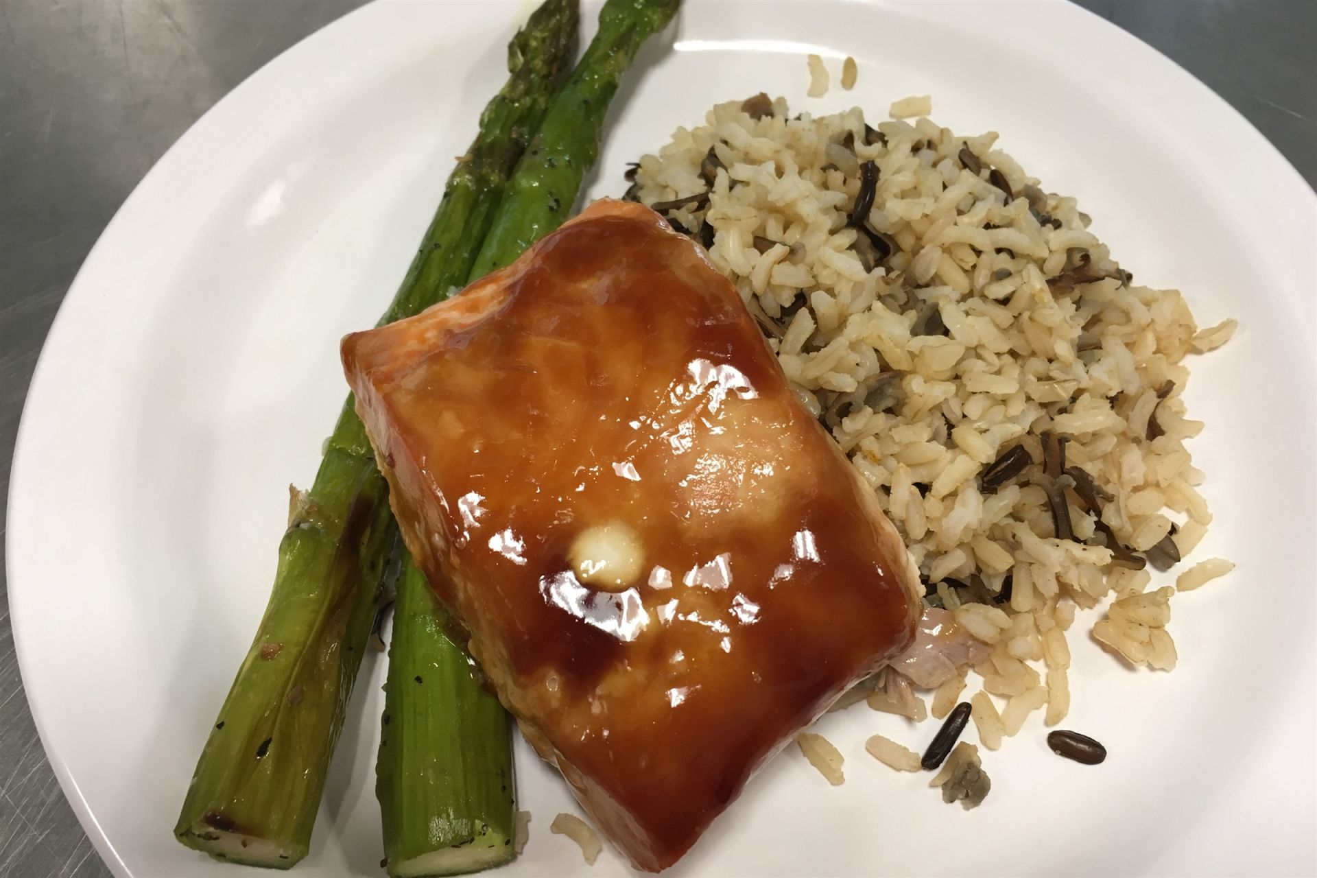 Soy glazed salmon with wild rice pilaf and asparagus.