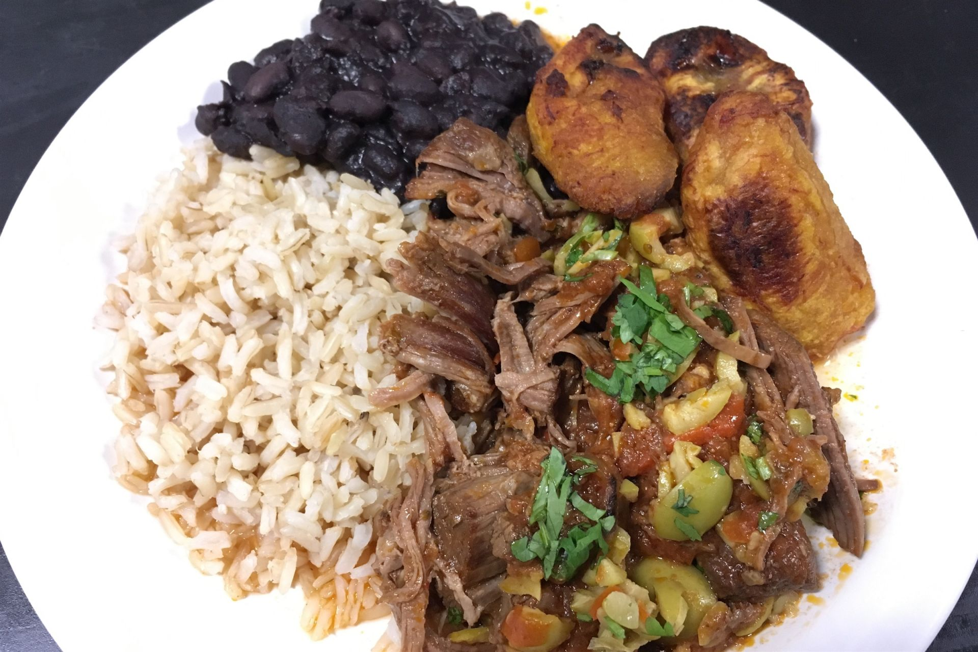 Cubian Ropa Vieja with brown rice, roasted plantains, and black beans.