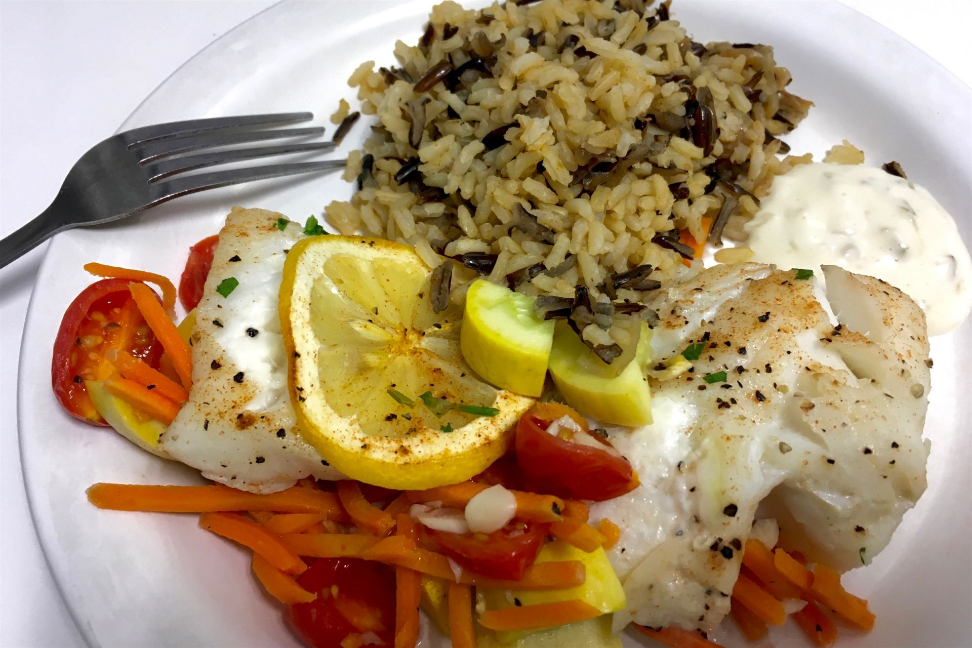 Roasted cod with vegetables and wild rice pilaf.
