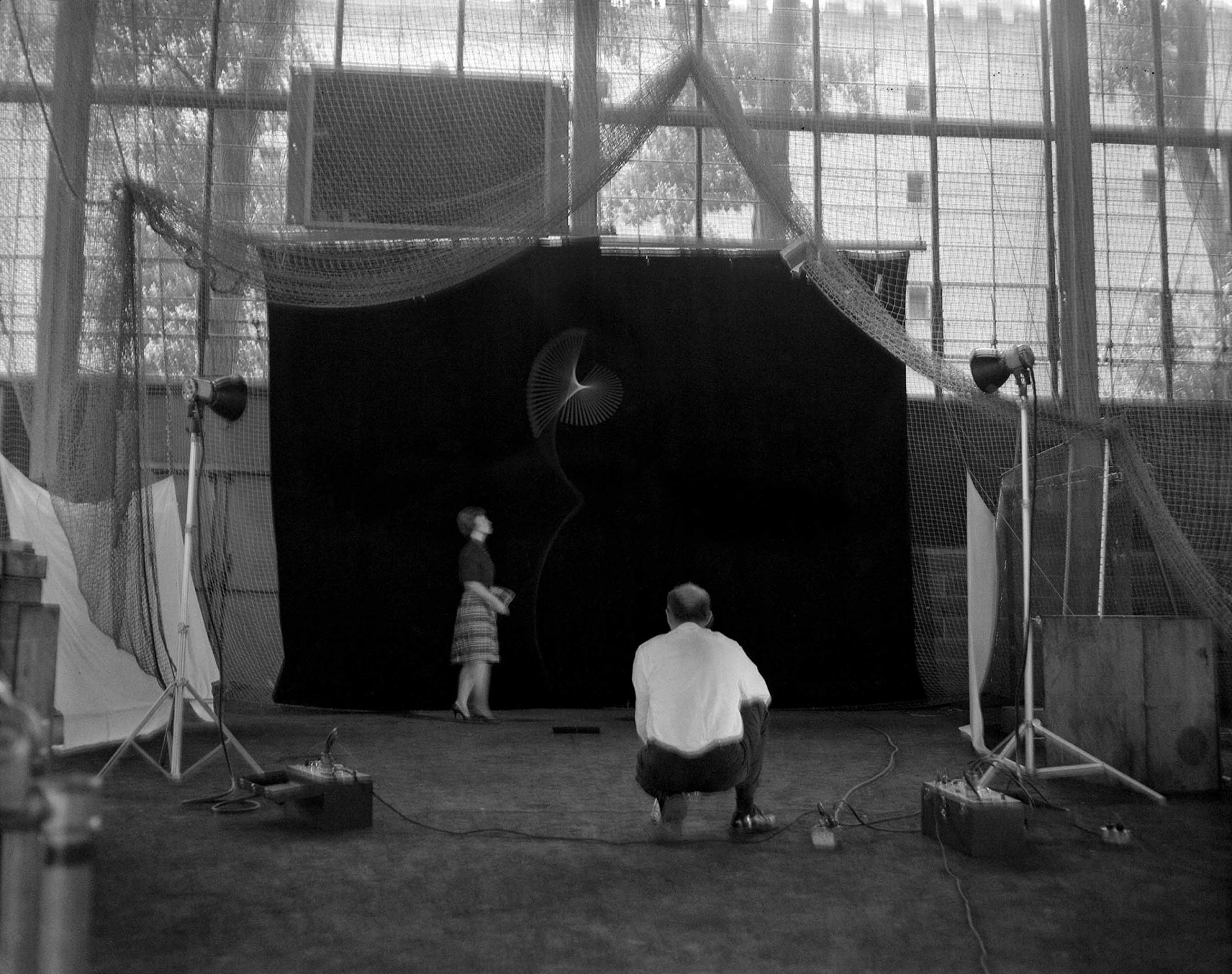 "<i>Edgerton Observes Baton Twirl,</i> 1965<br> pigment print<br> 6 x 7.5 inches<br> Edgerton often worked at MIT's athletic center when the scale of the activity required a much larger ""laboratory."" This photo documents the setup and preparation for a series of studies of baton tosses, showing the observer and his tools and subject. The duration of nearly a second reveals the concentration of both observer and observed."