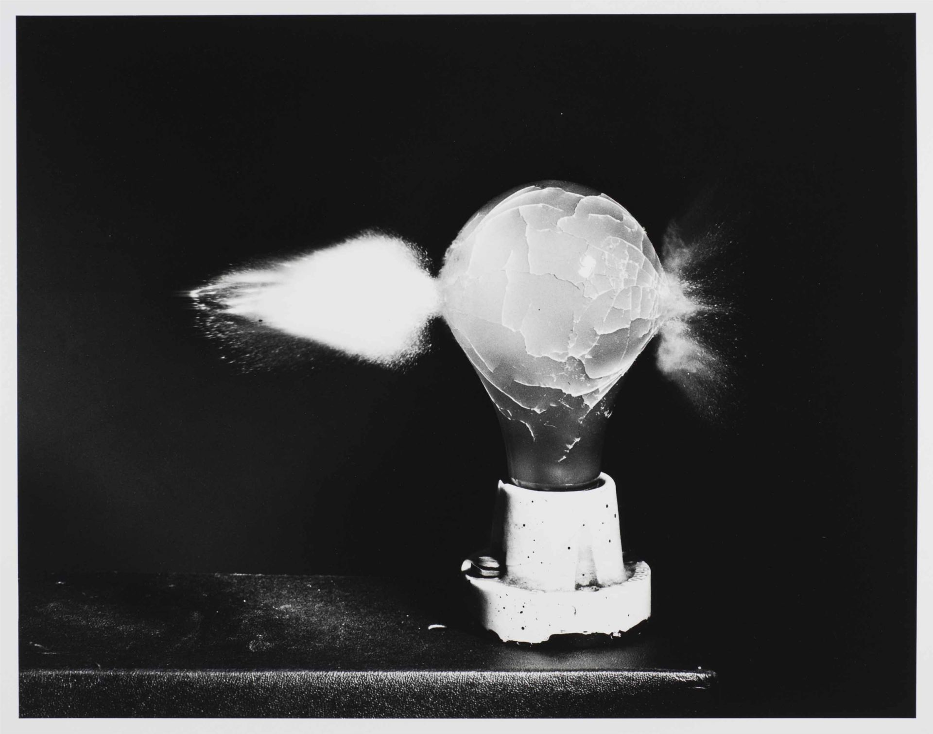 <i>Death of Lightbulb,</i> ca. 1935<br> gelatin silver print<br> 16 x 20 inches<br> Death of a Light Bulb is from a series of four photographs, one of which is on view in this exhibition. It reveals what happens when a .30-caliber bullet traveling at approximately 2,700 feet per second (over 1,800 miles per hour) encounters an electric light bulb. Whole light bulbs and complete face cards or aces were rarely to be found in the MIT Strobe Lab.