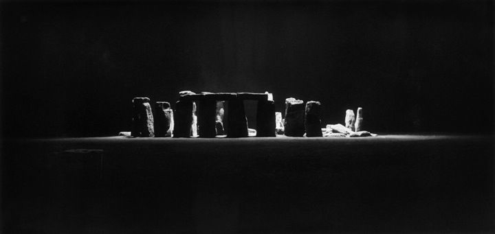 <i>Stonehenge at Night,</I> 1944<br> gelatin silver print<br> 11 x 17 inches<br> Illuminated by a one second, 50,000 watt flash in the bay of a night-flying airplane 1,500 feet above the ancient monoliths, Edgerton's pictures of Stonehenge served as a demonstration to the Allied commanders of the potential for nighttime reconnaissance photography. Edgerton was on the ground with a folding pocket camera braced on a fence post as the plane flew overhead. Simultaneously, the monument was recorded in perfect detail by a camera in the plane. The target was chosen because it was remote enough to allow the equipment to be tested without arousing unwanted interest. Edgerton has maintained an active curiosity about Stonehenge since he took this picture, which has appeared in virtually every publication about the monoliths.