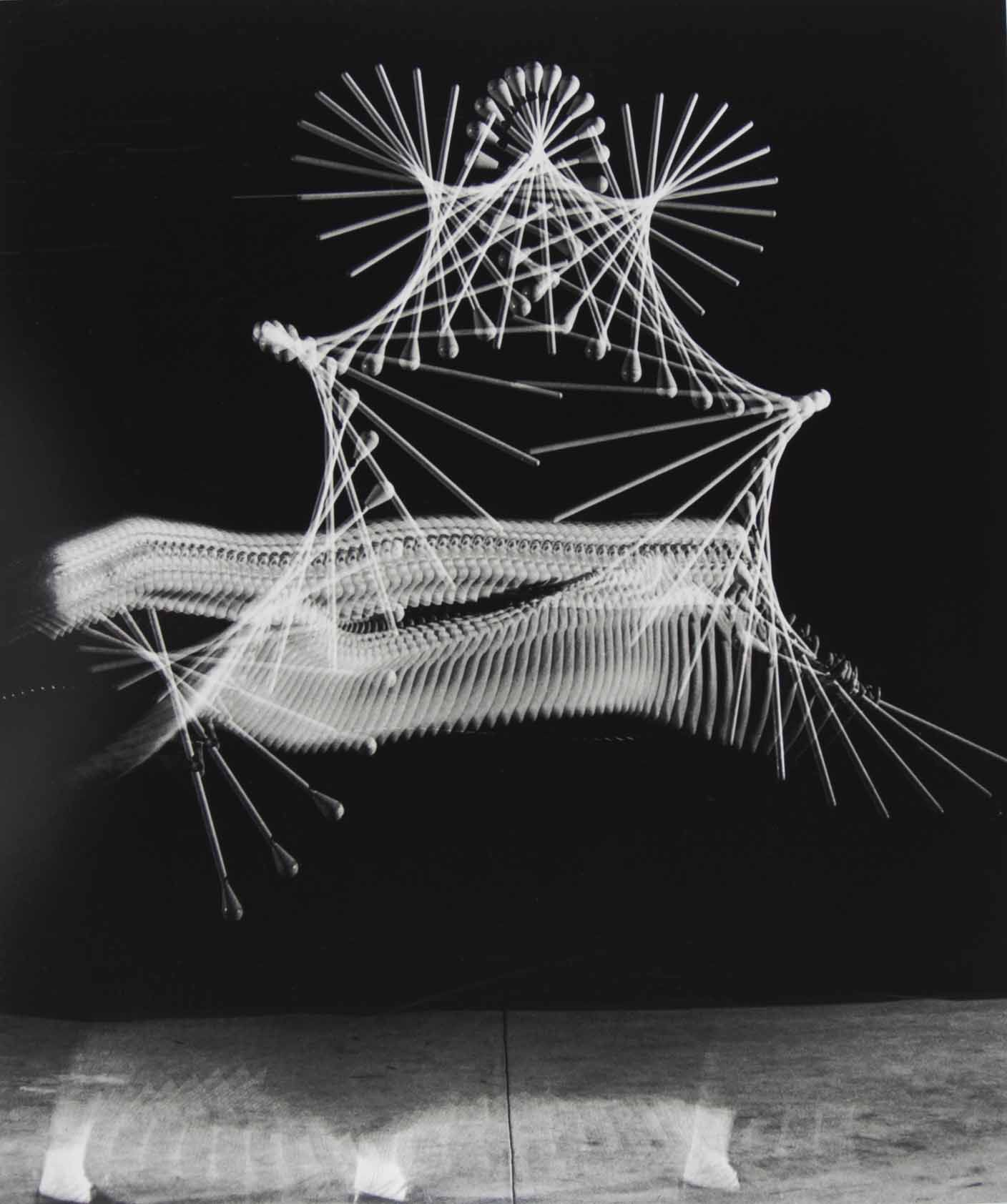 <i>Baton Multiflash (Ghost Feet),</i> 1953<br> gelatin silver print<br> 22 x 18 inches<br> With ghostly feet and only parts of her face showing, young Muriel Sutherland intently watches her baton as she throws it high in the air and moves rapidly forward to catch it. The multiflash was firing 60 times per second.