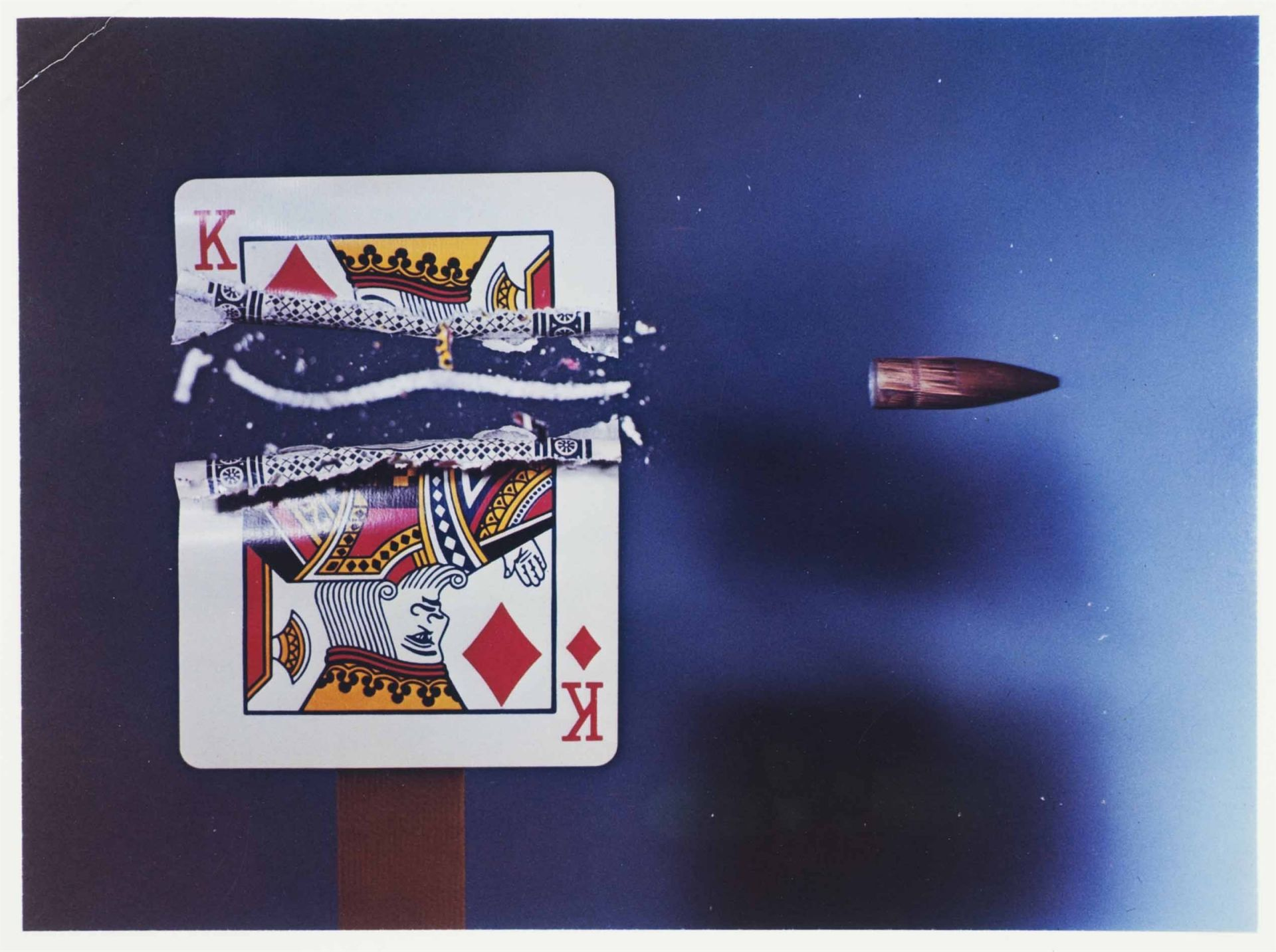 <i>Cutting the Card Quickly,</i> 1964<br> dye transfer<br> 16 x 20 inches<br> A .30 caliber bullet, traveling 2,800 feet per second, requires an exposure of less than 1/1,000,000 of a second to ensure the bullet is captured in the photograph before it exits the camera frame. Edgerton outdid the gun-slinging heroes of western movies by turning the card sideways when he shot through it. The rifling of the barrel caused the rotation of the projectile, which in turn carved out the S-shaped slice of card between the resultant upper and lower pieces of the card.