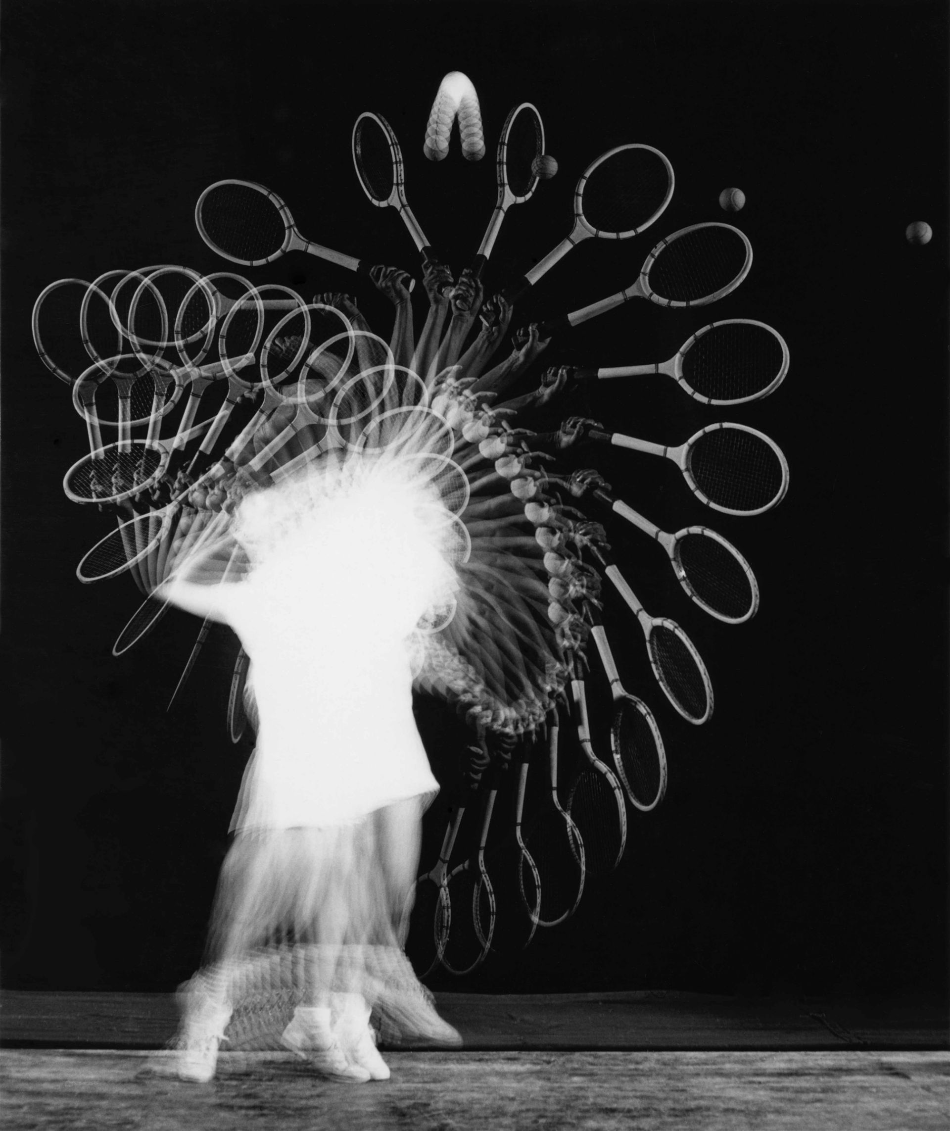 <i>Gussie Moran-Tennis Serve, Multiflash,</i> 1949<br> gelatin silver print<br> 12 x 16 inches<br> In 1949, Edgerton brought his strobes and other equipment to the Longwood Club to photograph the touring tennis stars. He was given a few minutes with each in an anteroom before they went out for their matches. Here, the outstanding British tennis player Gussie Moran tosses the ball into a perfect parabola for a power serve. Moran was especially well known for her sense of fashion style and her outfits - she refused to wear Doc's black kimono. In a typically inventive reaction, he determined that he would photograph action outside of her brilliantly white-clad body. In so many of Edgerton's best photographs, what seems like a perfect balance and form was a product of anticipation, timing, and much effort. Edgerton's ability to reveal the surprise of content with beautiful form allows the viewer to discover more than simple visceral pleasure.