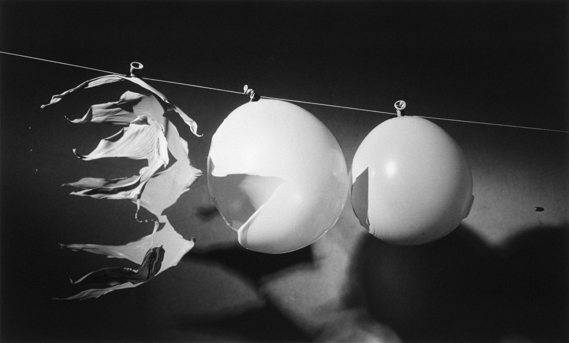 "<i>Bullet Through Three Balloons,</i> 1959<br> gelatin silver print<br> 13 x 17 inches<br> In one single picture, we see three consecutive stages of the bursting of balloons by a .22 caliber bullet. The sound from the rifle firing was picked up with a microphone, which ultimately triggered the microflash at less than one millionth of a second duration. Only the strobe and Edgerton's insatiable interest could reveal this almost instantaneous succession of events as clearly and totally different stages. The wonderful insight this picture provides is the result of Edgerton's keen eye and his knack for presenting phenomena as interesting and full of clues. The halls of Strobe Alley were often full of similar pictures accompanied by comments such as, ""What's Happening Here?"""