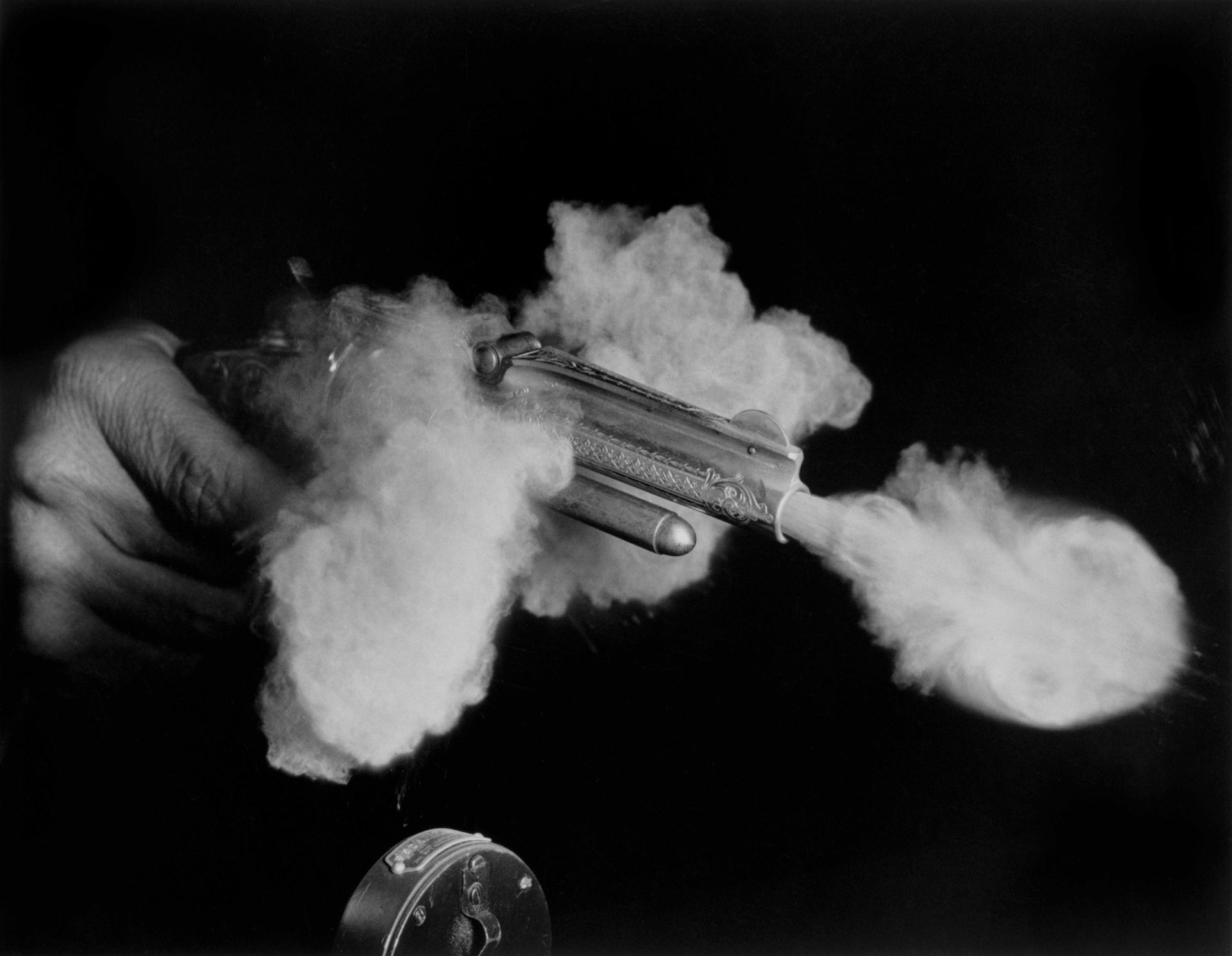 <i>Antique Gun Firing,</i> 1936<br> gelatin silver print<br> 16 x 20 inches<br> The 1878 revolver took its own picture as the explosion of the bullet going off triggered the microphone, visible in the foreground. The bullet is barely out of the muzzle, still hidden by the massive volume of smoke escaping the gun. This gives a visceral image of the enormous power released to power a bullet along its way.