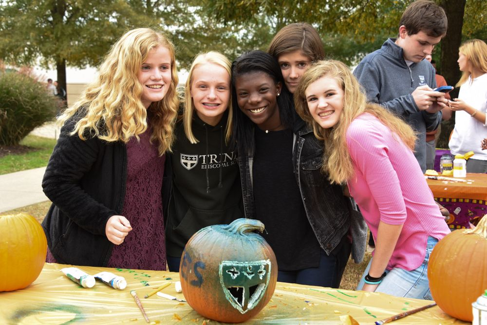Girls posing with decorated pumpkin
