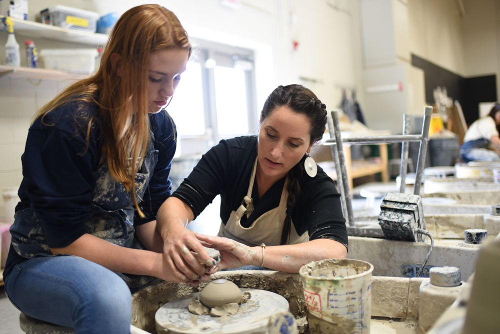 teacher and student throwing a bowl on the ceramics wheel