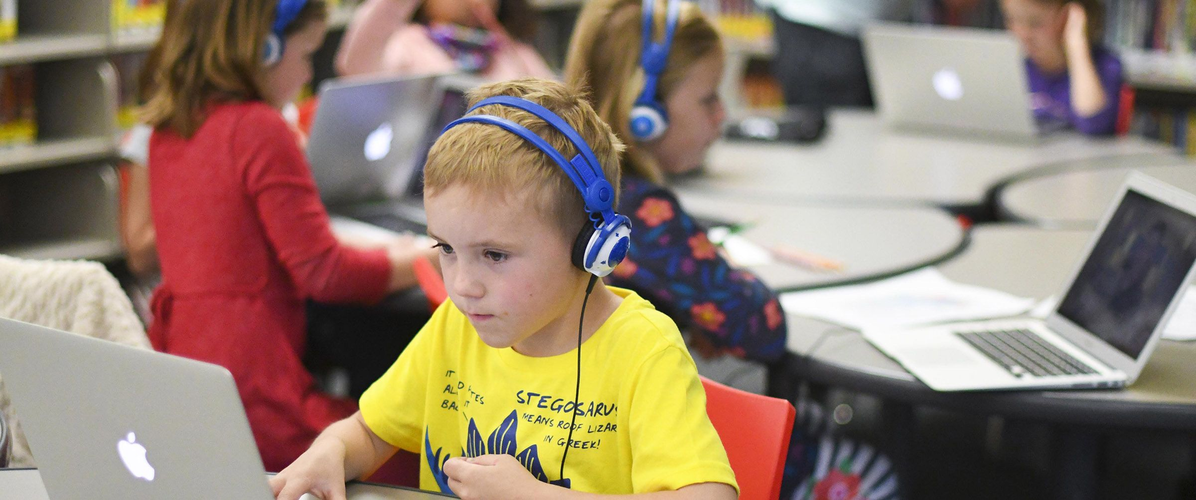 Boy on computer with headphones on in the Lower School Library. Colorado Academy, a top private PK-12 school in Denver.