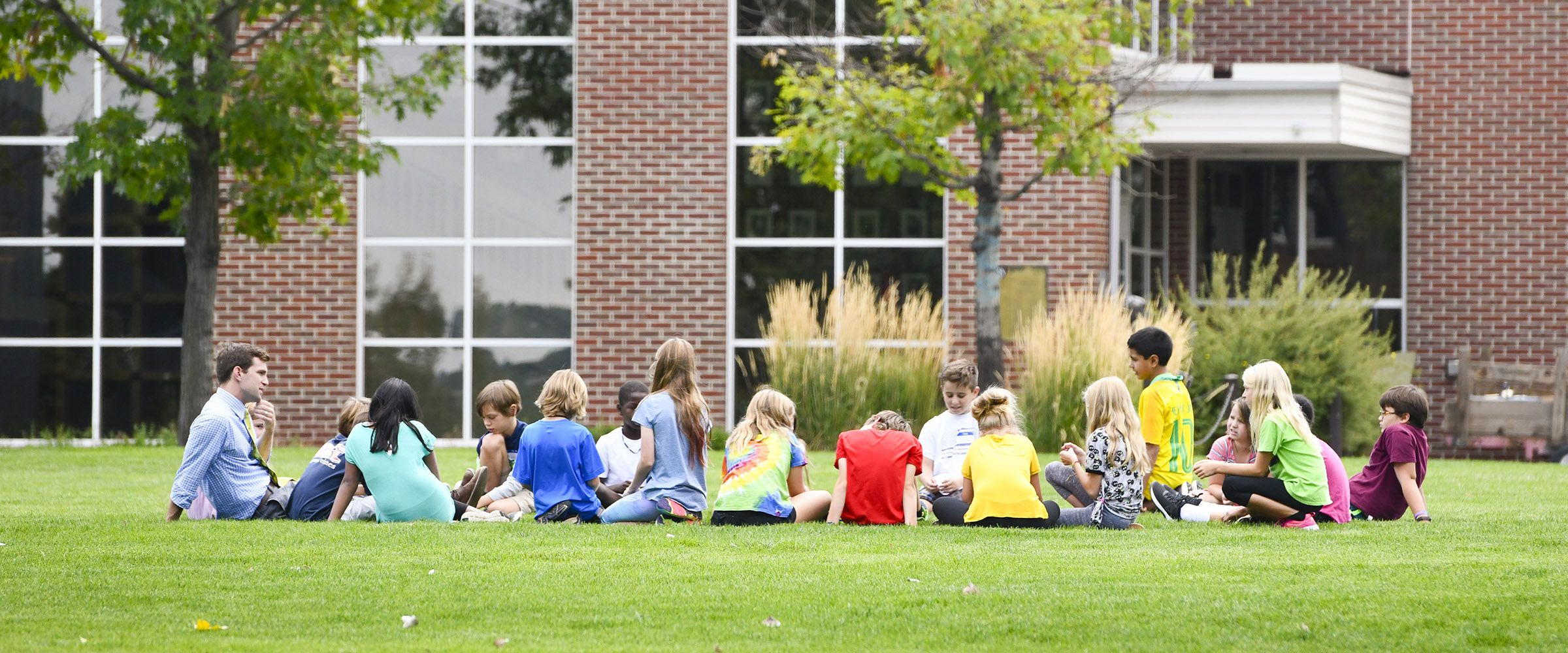 Fifth Grade class sitting outside in a circle on the lawn at Colorado Academy, a top private PK-12 school in Denver.