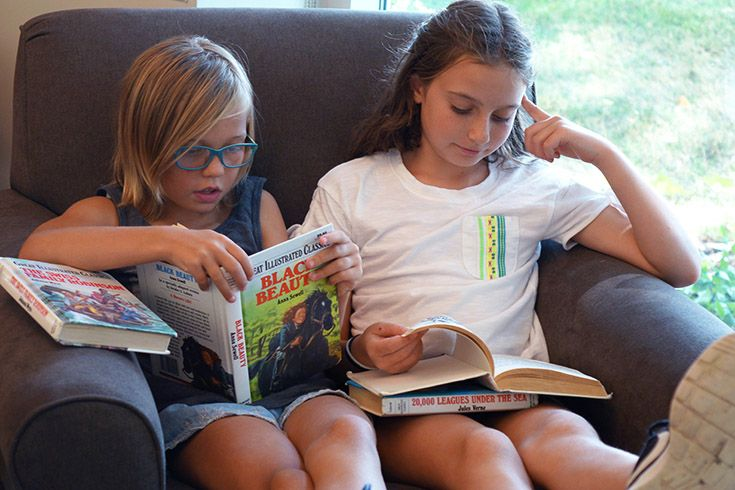 Girls reading in comfy chair