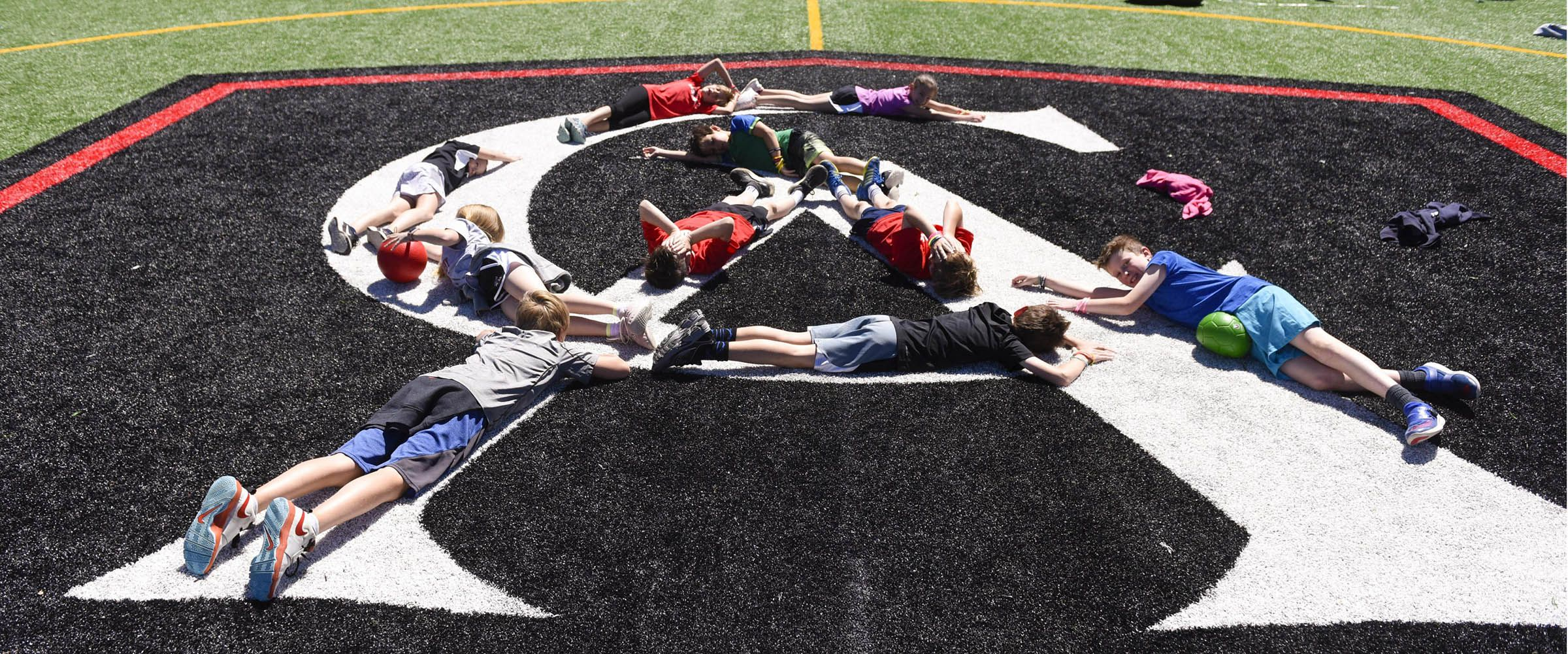 Students relaxing on the CA logo on the lacrosse field. Colorado Academy is a top PK-12 school in Denver.