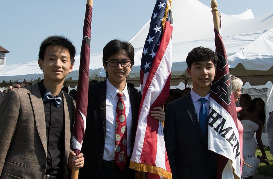 Tabor students holding flags during Commencement