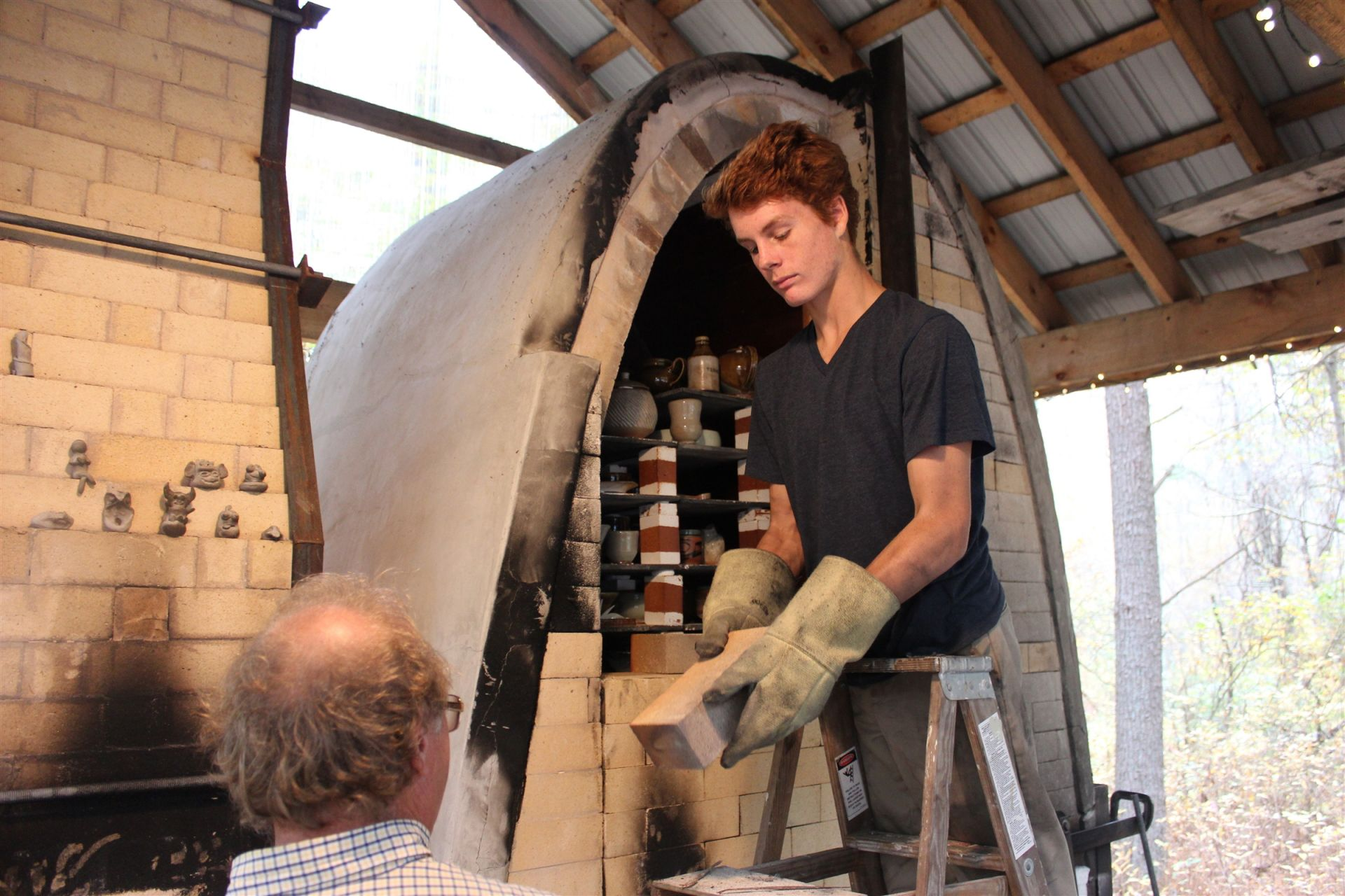 A student helps to load the wood kiln with faculty