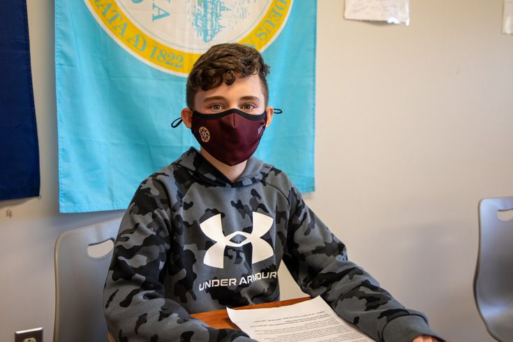 Severn School middle school student sits at a desk with a mask.