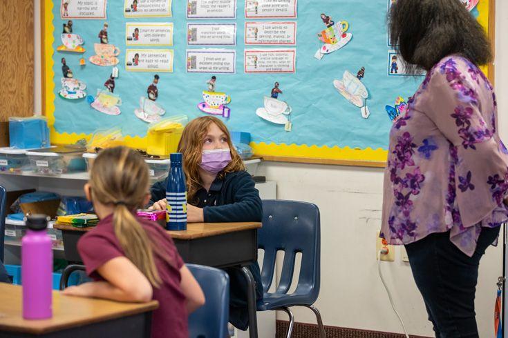 Severn School teacher talks to a student in class.