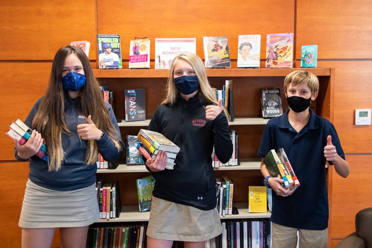Severn School 8th grade Battle of the Books Team posing with books in the library.