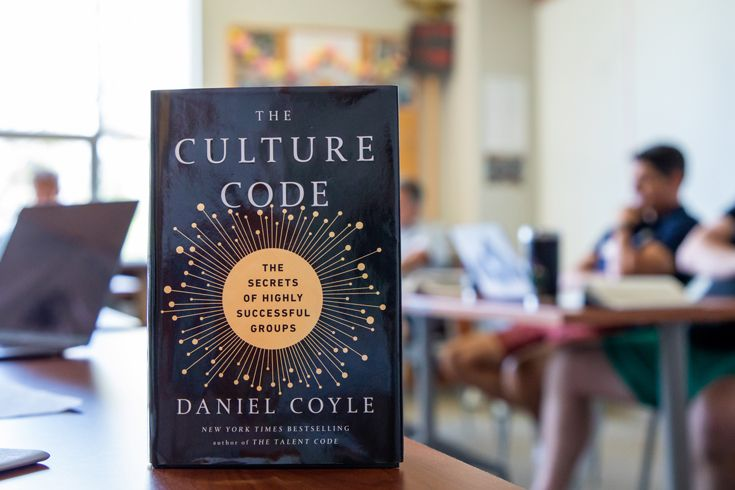 Photo of the book The Culture Code with teachers discussing in the background.