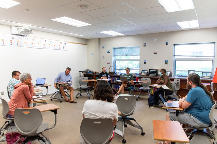 Severn School faculty and staff sitting at desks in a circle during a book discussion.