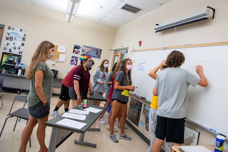 Severn School high school students work at the white board in a group.